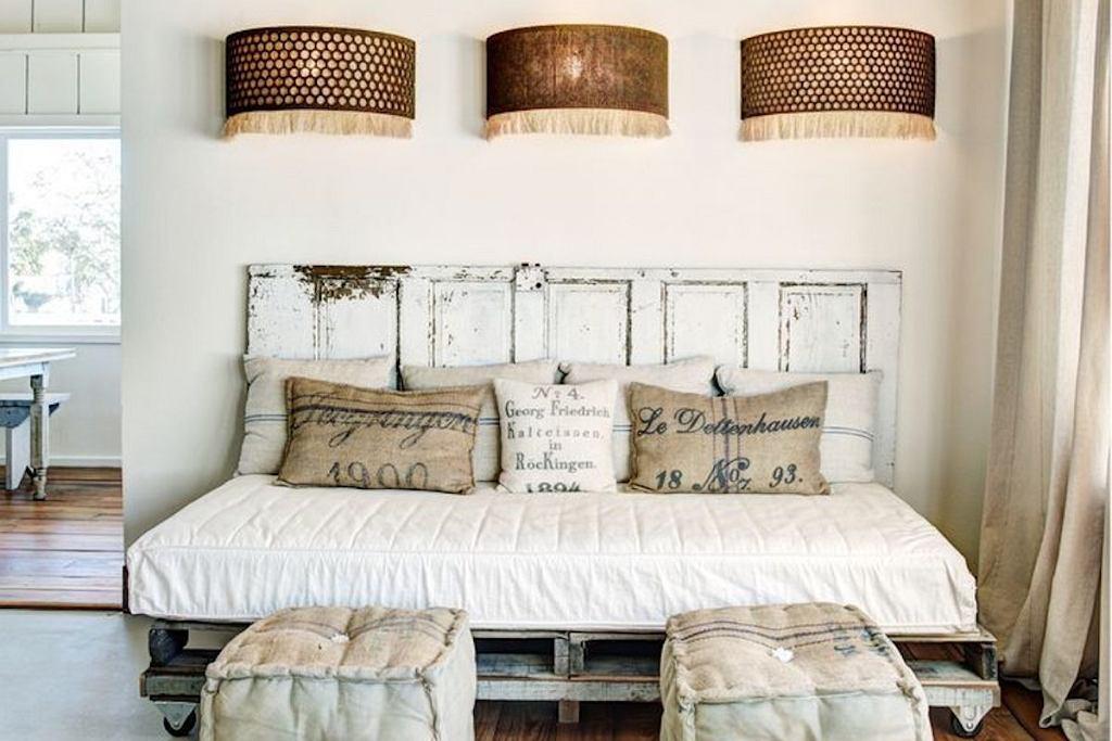 Łóżko z palet z zagłówkiem wykonanym ze starych drzwi drewnianych.