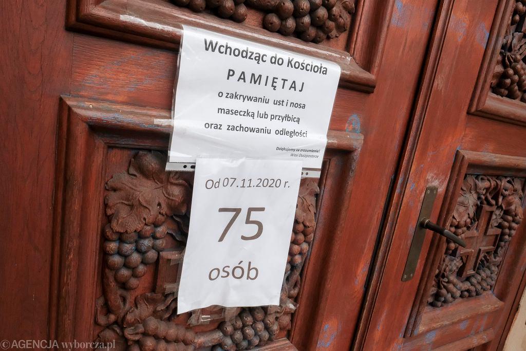 Ogłoszenie dotyczące obostrzeń na drzwiach kościoła Zmartwychwstania Pańskiego w Poznaniu