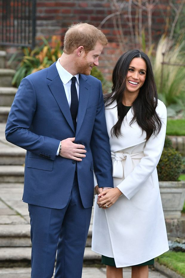 Britain's Prince Harry and Meghan Markle  pose for the media in the grounds of Kensington Palace in London, Monday Nov. 27, 2017. It was announced Monday that Prince Harry, fifth in line for the British throne, will marry American actress Meghan Markle in the spring, confirming months of rumors. (Dominic Lipinski/PA via AP)