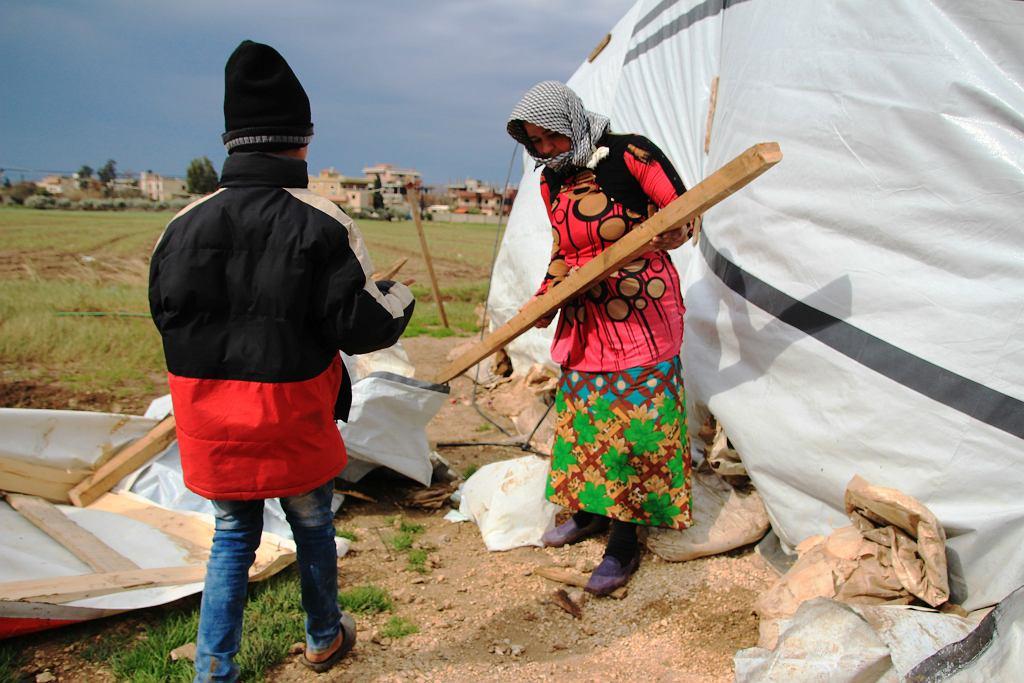 Uchodźczyni naprawia zniszczony przez wiatr namiot