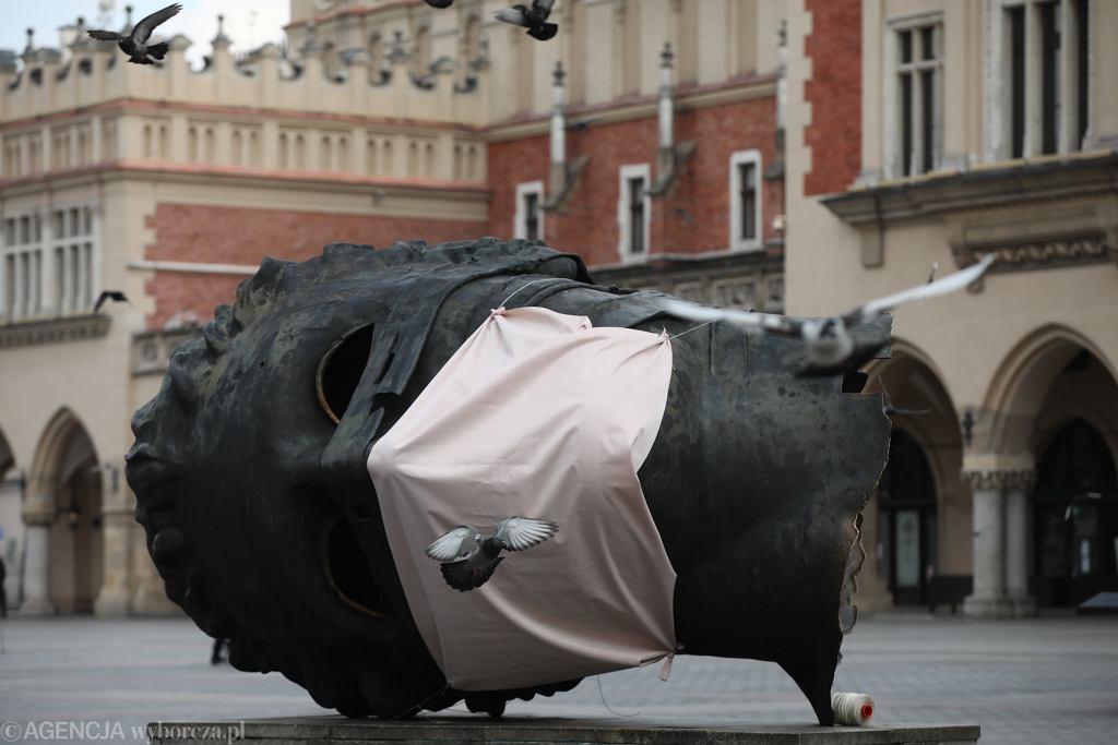 WKoronawirus w Polsce. Rzezba Igora Mitoraja na Rynku Glownym w Krakowie ubrana w maske