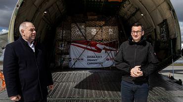 Premier rządu PiS Mateusz Morawiecki i minister aktywów państwowych Jacek Sasin na tle największego na świecie samolotu transportowego Antonow An-225 (i ładunku bezużytecznych maseczek zakupionych przez KGHM w Chinach) Warszawa, Okęcie, 14 kwietnia 2020