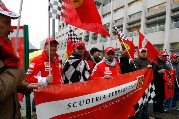 Supporters of Michael Schumacher hold Ferrari flags and a banner, to honour his 45th birthday, in front of the Grenoble hospital where the former seven-time Formula One champion is being treated after sustaining a head injury during a ski accident, Friday, Jan. 3, 2014. Schumacher has been in a medically induced coma since Sunday, when he struck his head on a rock while on a family vacation. (AP Photo/Claude Paris)