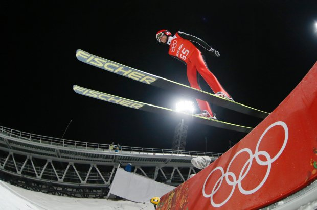 Switzerland's Simon Ammann makes an attempt from the normal hill of the men's ski jumping at the 2014 Winter Olympics, Thursday, Feb. 6, 2014, in Krasnaya Polyana, Russia. (AP Photo/Dmitry Lovetsky)