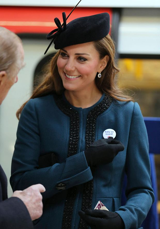 "REFILE - CORRECTING DATE    Britain's Catherine, Duchess of Cambridge holds a ""Baby on board!"" badge given to her during her visit to Baker Street underground station in London March 20, 2013. The visit was to mark the 150th anniversary of London Underground.     REUTERS/Chris Radburn/pool    (BRITAIN - Tags: ROYALS ENTERTAINMENT SOCIETY TRANSPORT)"