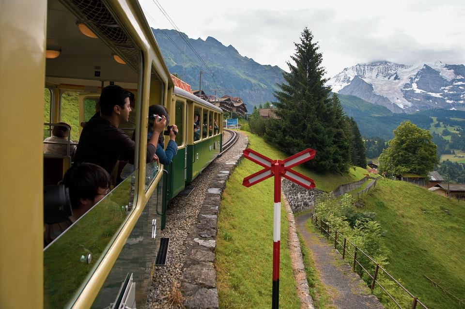 Turyści w górskiej kolejce przemierzającej alpejską przełęcz w kantonie berneńskim