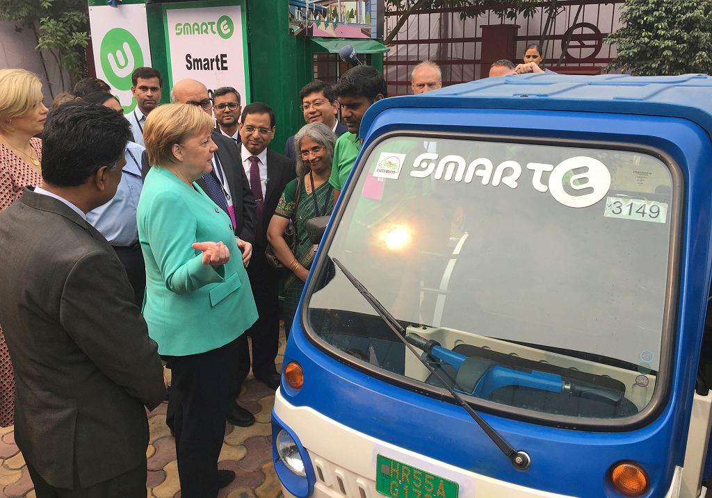 Angela Merkel ogląda elektryczny samochód obok stacji metra w New Delhi, stolicy Indii