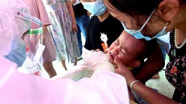 Pracownik medyczny pobiera próbki wymazu od dziecka podczas masowych testów na COVID-19 w bloku mieszkalnym w Wuhan w prowincji Hubei w środkowych Chinach. Chiny ogłosiły masowe testowanie na koronawirusa w Wuhan ponieważ wariant delta dotarł do ??miasta, w którym choroba została wykryta po raz pierwszy pod koniec 2019 roku