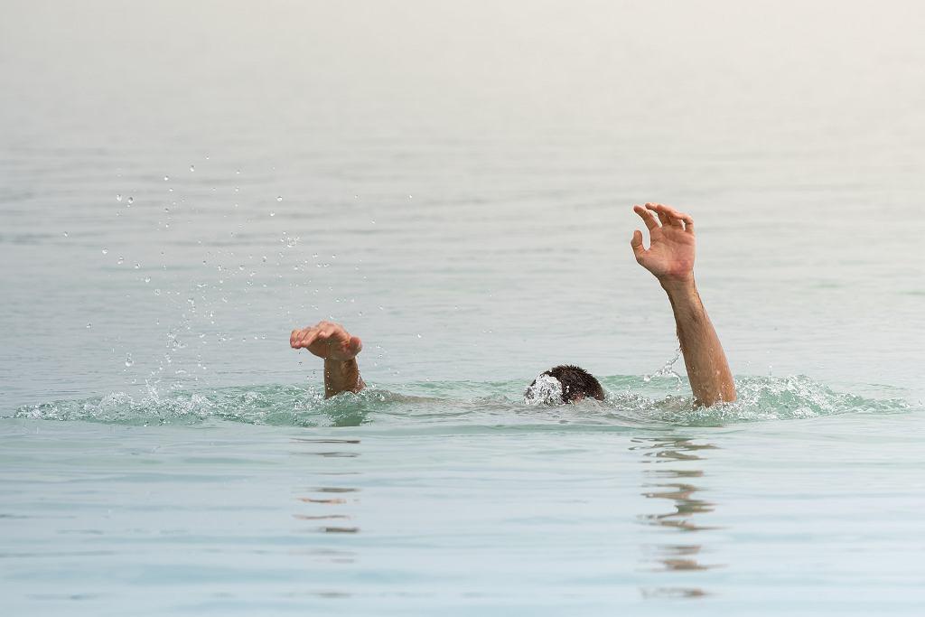 Młody mężczyzna co chwila zanurzał się głębiej w wodzie