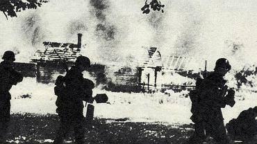 Niemieccy żołnierze na tle płonącej wioski w ZSRR, II wojna światowa