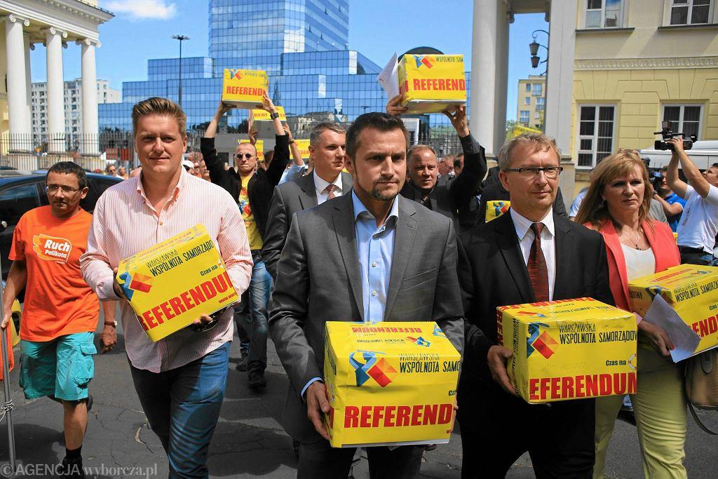 Piotr Guział, zbuntowany burmistrz stołecznego Ursynowa (na zdjęciu w środku), dostarcza komisarzowi wyborczemu pudła z podpisami pod wnioskiem o referendum w sprawie odwołania prezydent Warszawy Hanny Gronkiewicz-Waltz.