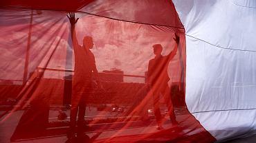 Robotnicy wieszają flagę narodową na elewacji Spodka