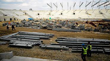 Przy al. Piłsudskiego trwa stawianie nowego stadionu dla Widzewa. Obiekt osiągnął już imponujące rozmiary - postawiono wszystkie trybuny, a na nich płyty audytoryjne, na których montowane będą krzesełka. Trwa też budowa dachu, który w największym stopniu pokrywa trybunę zachodnią. To właśnie w niej poziom prac jest najbardziej zaawansowany. Miejsce, na którym kiedyś znajdzie się murawa, na razie służy jako przechowalnia materiałów budowlanych. W piątek plac budowy mogli odwiedzić kibice. Na krótką wycieczkę po obiekcie zdecydowało się około 40 osób. Fani najchętniej robili sobie zdjęcia z wysokości trybun, plecami do boiska. Budowa stadionu Widzewa kosztować będzie ponad 113 mln zł. Kolejne 24 mln zł zostanie wydane na przebudowę okolicznych dróg. Obiekt będzie mógł pomieścić nieco ponad 18 tysięcy kibiców. Koniec inwestycji zaplanowano na listopad.