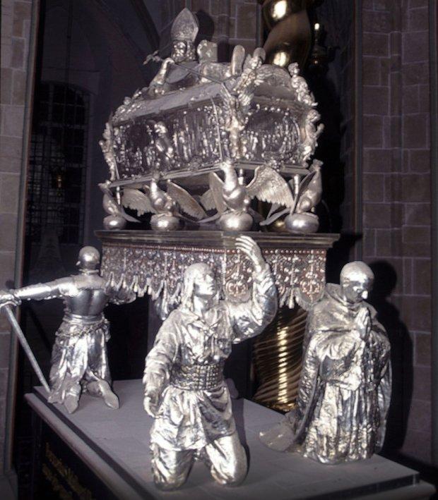 Odrestaurowany relikwiarz. Oryginał powstał w 1662 r. w gdańskiej pracowni Piotra van der Rennena. Tworzyły go zawierająca domniemane szczątki świętego trumienka przykryta wieczkiem, na którym spoczywa półleżąca postać męczennika w stroju biskupim z pastorałem. Trumienkę dźwiga sześć orłów, a całość podtrzymują figury rycerza, duchownego, mieszczanina i chłopa symbolizujące stany Rzeczypospolitej. Dopiero po włamaniu do katedry gnieźnieńskiej w wielu kościołach zaczęto stosować zabezpieczenia elektroniczne; wcześniej dzieła sztuki sakralnej zabezpieczano kłódkami i kratami.