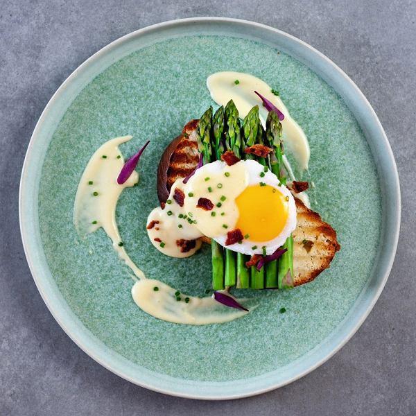 Maślany tost zchałki zblanszowanymi szparagami, jajkiem poche, czipsami zboczku isosem holenderskim