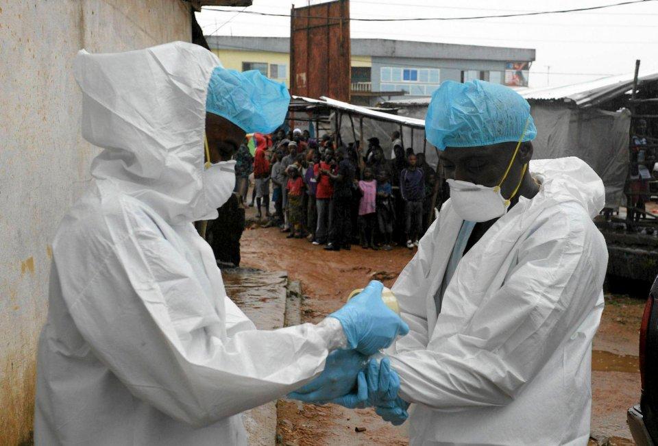 Pracownicy służby zdrowia wkładają ochronne ubrania. Będą przenosić porzucone ciało ofiary wirusa.