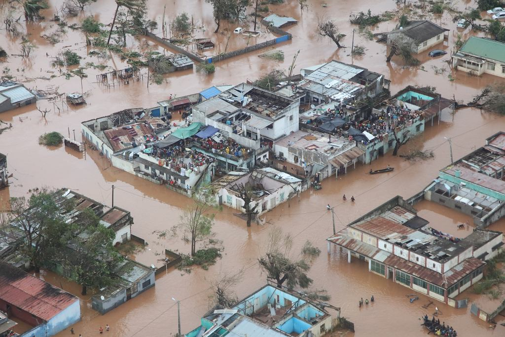People take refuge on the roofs of buildings following flooding caused by Cyclone Idai in Mozambique