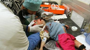 Lekarze udzielają pomocy dziecku rannemu w wyniku nalotów na Aleppo