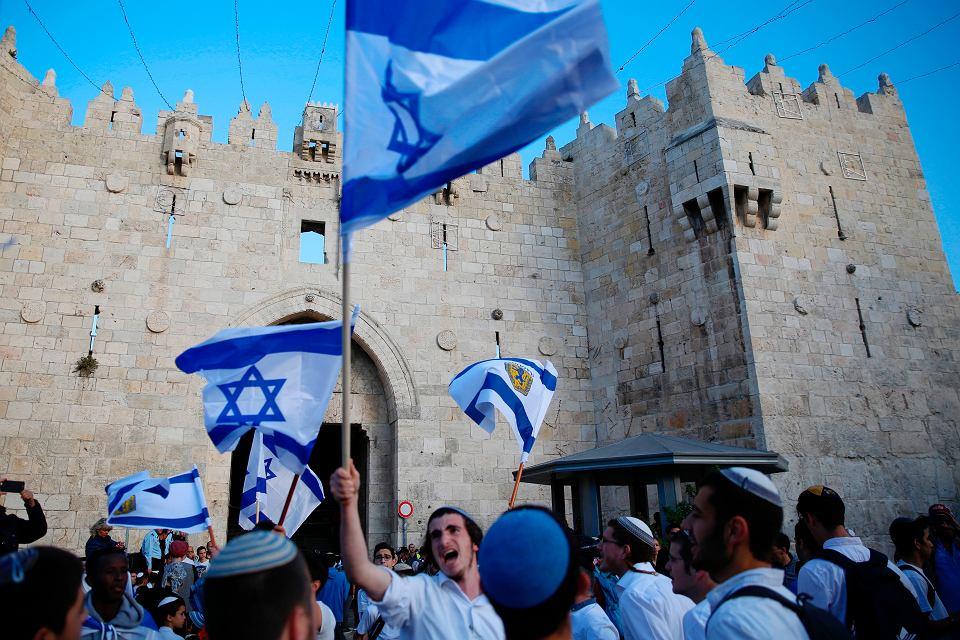 Młodzi Izraelczycy wymachują narodowymi flagami przed Bramą Damasceńską w starej części Jerozolimy