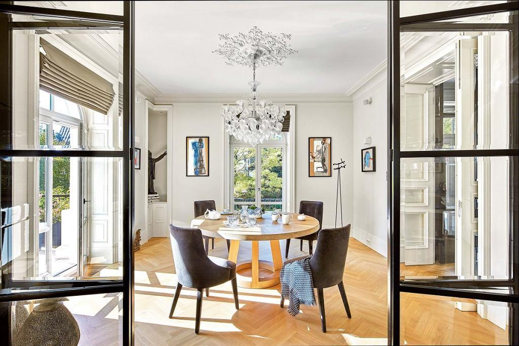 Stół wjadalni pochodzi zholenderskiej manufaktury Odesi. Krzesła Maxalto. Przeszklone drzwi z metalu oddzielają kuchnię od jadalni.