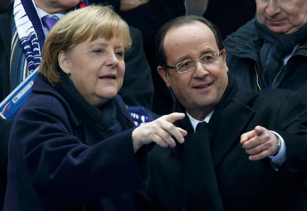 France's President Francois Hollande (R) points with German Chancellor Angela Merkel as they attend an international friendly soccer match betweeen France and Germany at the Stade de France stadium in Saint-Denis, near Paris, February 6, 2013.         REUTERS/Charles Platiau (FRANCE  - Tags: SPORT SOCCER POLITICS)   SLOWA KLUCZOWE: :rel:d:bm:LR1E9261NSDKG
