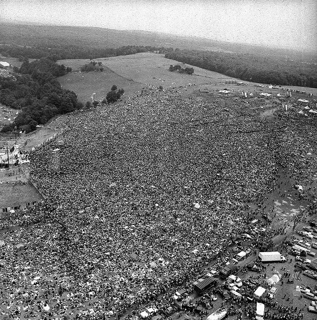 FILE - This Aug. 16, 1969 file photo shows a crowd of about 400,000 people attending the Woodstock Music and Arts Festival in Bethel, N.Y. Woodstock was staged 80 miles northwest of New York City on a bucolic hillside owned by dairy farmer Max Yasgur. It was great spot for peaceful vibes, but miserable for handling the hordes coming in by car. Fifty years later, memories of the rainy weekend Aug. 15-18, 1969, remain sharp among people who were in the crowd and on the stage. (AP Photo, File)