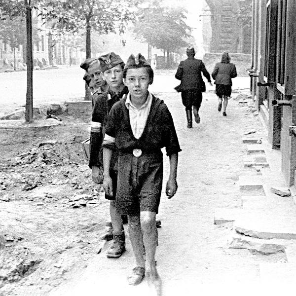 Sierpień 1944, Śródmieście Północne. Chłopcy stoją na ul. Sienkiewicza. Na dalszym planie wylot ul. Zgoda z ufortyfikowanym wejściem do budynku firmy Gebethner i Wolff przy Sienkiewicza 9