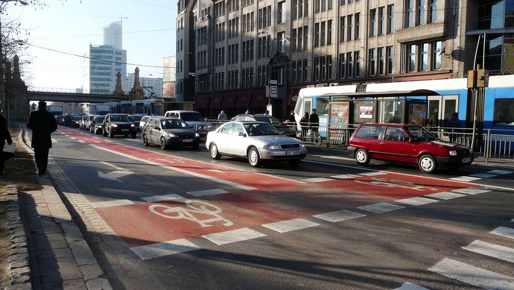 Pas rowerowy pomiędzy pasami rozplotu dla aut oraz śluza rowerowa na ulicy Powstańców Śląskich we Wrocławiu