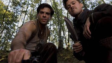 Jeden z oprawców (ps. 'Żydowski Niedźwiedź' - Eli Roth, z lewej) specjalizuje się w roztrzaskiwaniu głów nazistom kijem bejsbolowym, a znakiem firmowym bandy sierżanta Aldo Raine (Brad Pitt, z prawej) jest skalpowanie ofiar. Nieliczni, którzy uchodzą z życiem, dostają na pamiątkę wyciętą nożem na czole swastykę