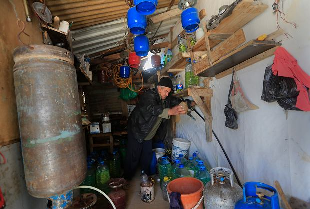 A Syrian displaced man Mohammed Zakaria, 53, who fled his Syrian hometown of Homs in 2012, works at his gas and oil shop which is at the entrance of his tent at a refugee camp, in Bar Elias, in eastern Lebanon