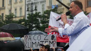 Walczący o reelekcję Andrzej Duda na kampanijnym szlaku. Agituje na Rynku Głównym, z transparentem Młodzieżowego Strajku Klimatycznego w tle. Kraków, 21 czerwca 2020