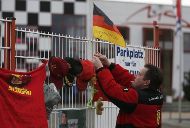 A fan fixes a flag marking the 45th birthday of seven-times former Formula One world champion Michael Schumacher, to a fence outside Schumacher's cart racing track, in the western city of Kerpen January 3, 2014. Schumacher was in a stable condition on Wednesday, three days after suffering brain injuries in a skiing accident, his agent Sabine Kehm said outside the French hospital treating him.  Schumacher, who turns 45 today, is battling for his life after slamming his head against a rock while skiing off-piste in the French resort of Meribel on Sunday.   REUTERS/Ina Fassbender (GERMANY - Tags: SPORT MOTORSPORT DISASTER HEALTH)