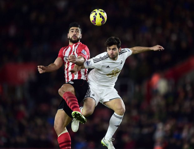 Southampton's Graziano Pelle, left, and Swansea's Federico Fernandez battle for the ball during their English Premier League soccer match at St Mary's, Southampton, England, Sunday, Feb. 1, 2015. (AP Photo/Adam Davy, PA Wire)     UNITED KINGDOM OUT      -    NO SALES     -     NO ARCHIVES SLOWA KLUCZOWE: pne