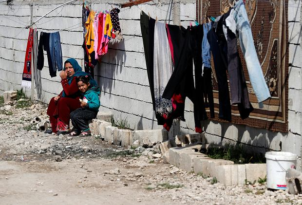 A Syrian displaced woman with her daughter sit outside their tent, as they enjoying the sunny weather at a refugee camp, in Bar Elias, in eastern Lebanon
