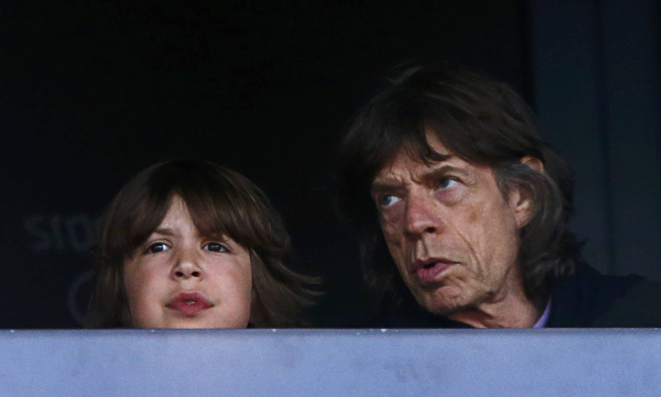 Mick Jagger of the Rolling Stones sits with his son Lucas as they watch the evening's athletics events during the London 2012 Olympic Games at the Olympic Stadium August 6, 2012.   REUTERS/Eddie Keogh (BRITAIN  - Tags: SPORT OLYMPICS SPORT ATHLETICS ENTERTAINMENT TPX IMAGES OF THE DAY)