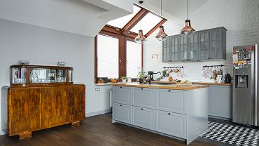 W salonie zastosowano wiszące lampy w industrialnym stylu i stylowy stary kredens.