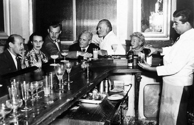 """EH 5084P  not dated, ca. 1955 La Floridita, Havana, Cuba. Roberto Herrera, Byra """"Puck"""" Whittlesey, John """"Bumby"""" Hemingway, Spencer Tracy, Ernest Hemingway, and Mary Hemingway. Please credit: """"Ernest Hemingway Photograph Collection, John Fitzgerald Kennedy Library, Boston.""""   SLOWA KLUCZOWE: Ernest Miller Hemingway Mary Welsh Hemingway Spencer Tracy Havana Cuba La Florida bar lounge cocktail"""