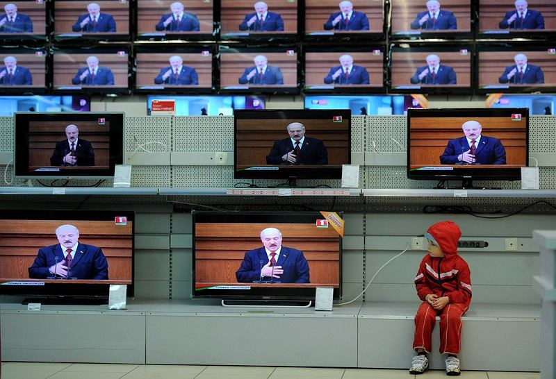 Chłopiec ogląda przemawiającego do parlamentu i narodu prezydenta Aleksandra Łukaszenkę w jednym ze sklepów w Mińsku