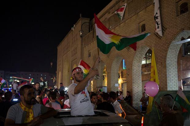 Mężczyzna macha kurdyjską flagą na ulicach miasta Irbil, po referendum w Iraku