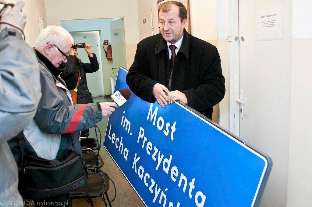 Autorem pomysłu jest Bogdan Dzakanowski. Na zdjęciu odbiera z komisariatu policji tablicę z nazwą mostu im. Lecha Kaczynskiego