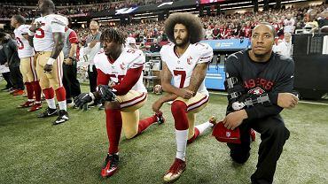 Colin Kaepernick (w środku) demonstracyjnie klęczy z kolegami, zamiast stać na baczność podczas hymnu przed meczem NFL