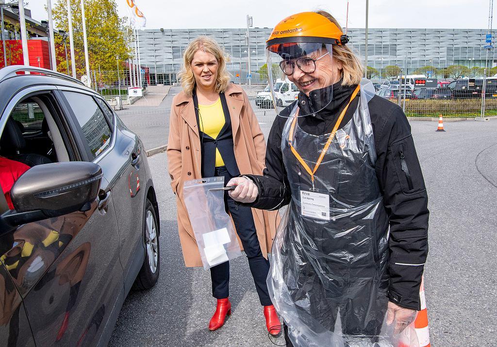 Szwedzka minister zdrowia Lena Hallengren (z tyłu) przygląda się pobieraniu próbek do testu na obecność koronawirusa, Alvsjo, Sztokholm, 6.05.2020