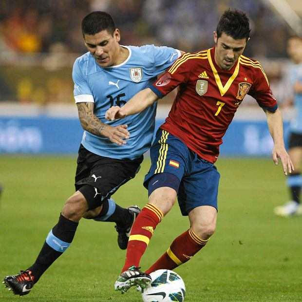 Uruguay's Cristian Rodriguez (L) fights for the ball with Spain's David Villa during their international friendly soccer match in Doha February 6, 2013.REUTERS/Mohammed Dabbous (QATAR - Tags: SPORT SOCCER) SLOWA KLUCZOWE: :rel:d:bm:GF2E9261MHF01