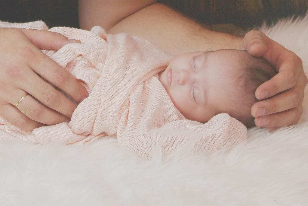 Rozwój dziecka: śpiące niemowlę w objęciach rodzica. Zdjęcie ilustracyjne