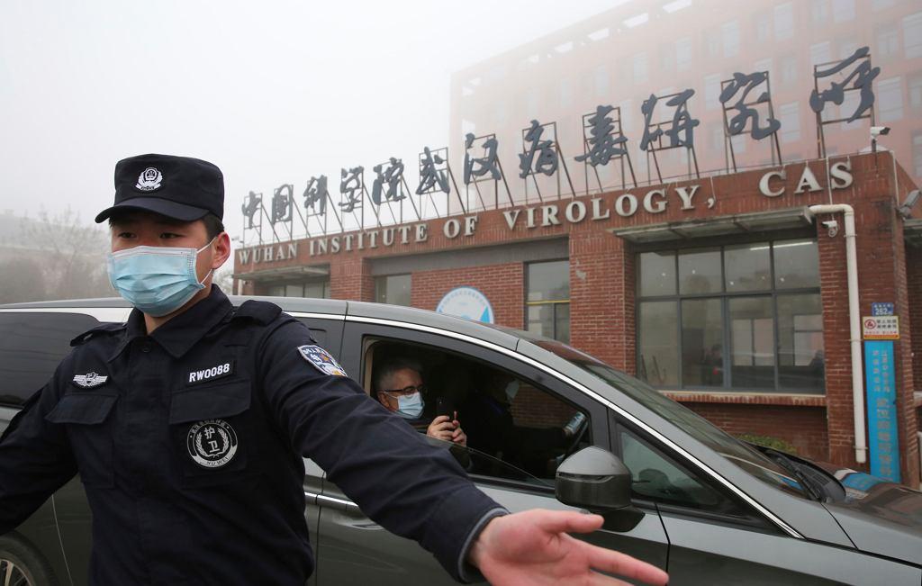 Ochroniarze pilnuje wjazdu do Instytutu Wirusologii w Wuhanie, w tle samochód wiozący ekspertów Światowej Organizacji Zdrowia (WHO), 3 lutego 2021 roku. Członkowie zespołu badawczego WHO podjęli się zbadania źródeł pandemii wirusa Covid-19.