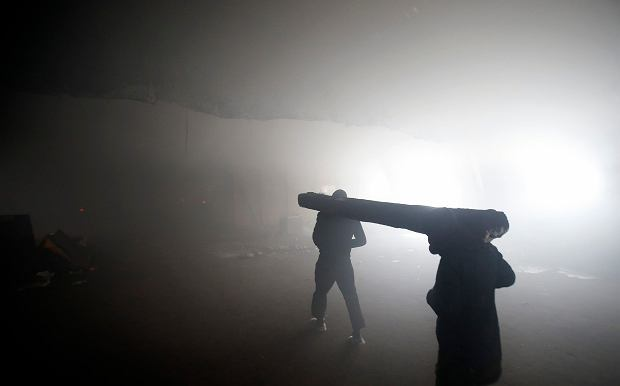 Migranci niosą drewno na opał w opuszczonym budynku w Serbii