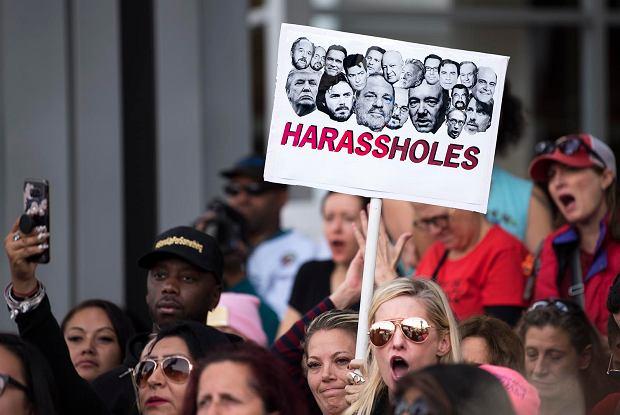 Wiec ruchu #MeToo przeciwko molestowaniu seksualnemu, Los Angeles, listopad 2017 r. Na plakacie pod zdjęciami oskarżanych o to ludzi filmu i polityki napis, który jest zbitką słów: 'harassment' i 'asshole' (molestowanie i dupek)