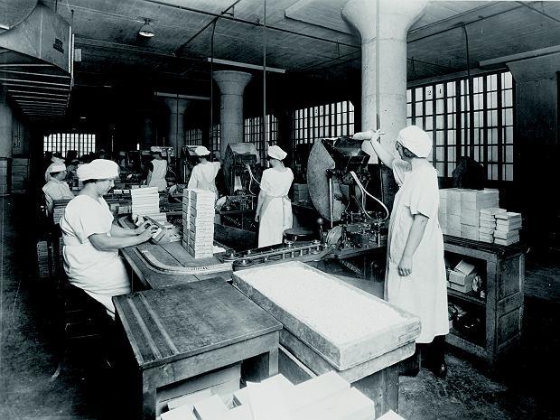 Linia pakowania gum do żucia American Chicle Company w fabryce naBrooklynie w 1923 r. Chicle to naturalna guma z drzew. Thomas Adams, który pracował jako sekretarz u meksykańskiego prezydenta Santa Anny, zauważył, że ten żuje chicle. Postanowił zrobić zniej gumę na. opony. Gdy mu nie wyszło, opatentował gumę