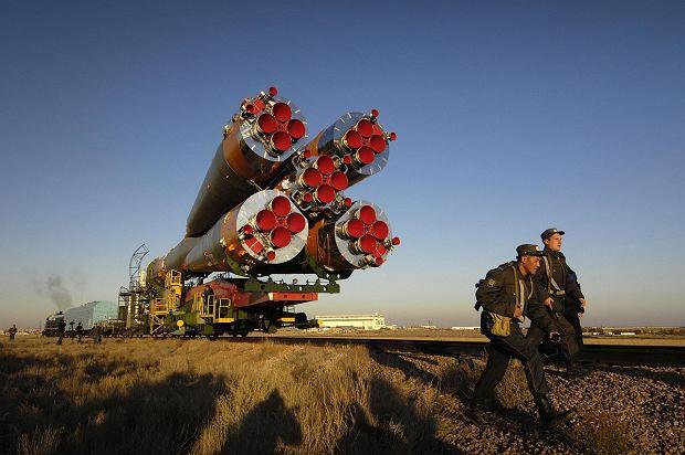 Rakieta Sojuz transportowana na stanowisko startowe na kosmodromie Bajkonur. W centrum silnik pierwszego stopnia. Dookoła cztery boostery