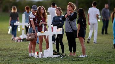 Bliscy modlą się na szkolnym boisku. Krzyż upamiętnia jedną z ofiar strzelaniny w Marjory Stoneman Douglas High School, w Parkland na Florydzie. Relegowany uczeń zamordował z broni palnej 17 osób. USA, 16 lutego 2018
